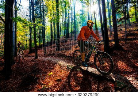 Cycling man riding on bike at sunset mountains forest landscape. Cycling MTB enduro flow trail track. Outdoor sport activity.