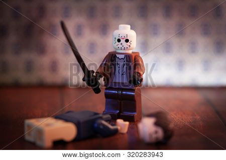 AUG 31 2019: Horror film Friday the 13th killer Jason Voorhees Lego style minifig with machete and headless victim at Camp Crystal Lake