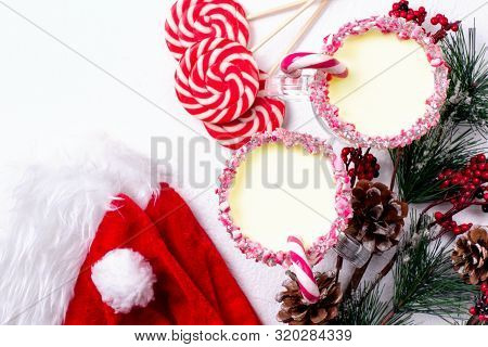Two Glasses Of Eggnog With Candy Cane, Santa Hat And Christmas Tree On White Background.