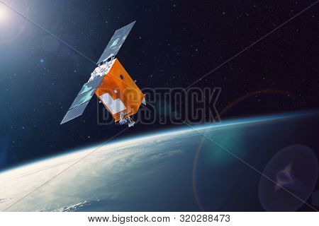 Space Satellite Orbiting Earth Low Polar Orbit. Bright Light From The Sun And Glare In The Frame. El