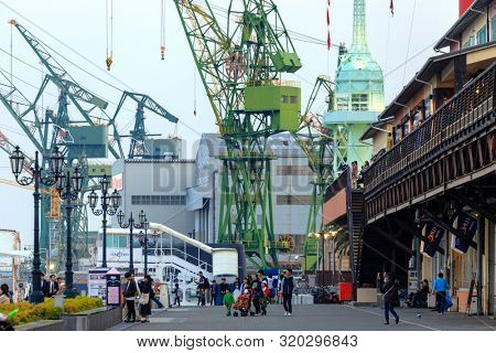 KOBE, JAPAN, APRIL 4, 2019 : People are walking in the Kobe harbour area surrrounded by large cranes .