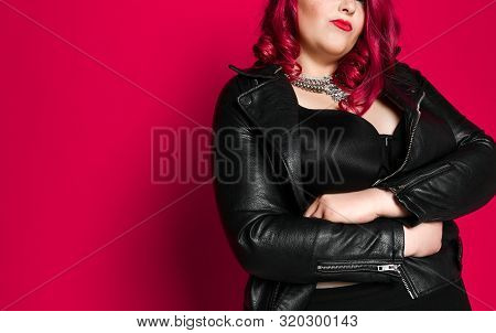 Portrait Of Beautiful Plus Size Sexy Red-haired Woman In Black Leather Jacket And Black Bra, On Pink