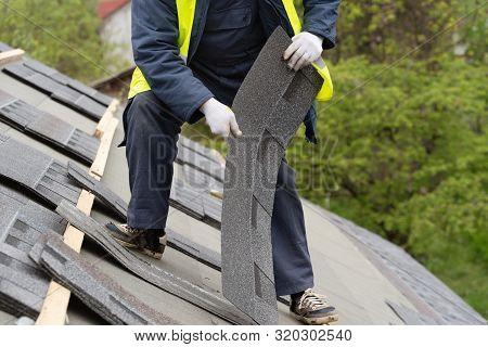 Professional And Skilled Roofer Worker In Special Protective Work Wear Installing Asphalt Or Bitumen