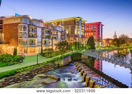 Downtown cityscape of of Greenville, South Carolina, USA on the Reedy River at dusk.