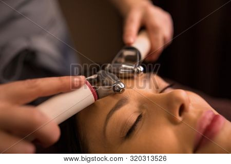 people, beauty, cosmetology and technology concept - close up of beautiful young woman having needle free mesotherapy or hydradermie facial treatment by microcurrent firming device in spa poster
