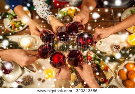 holidays and celebration concept - close up of friends having christmas dinner at home, drinking red wine and clinking glasses over snow