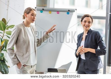 two smiling businesswomen in formal wear standing near flipchart in office poster