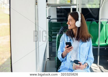 Young Woman Sits In The Modern City Bus, Listens To Music, Drinks Coffee And Looks Out From The Wind
