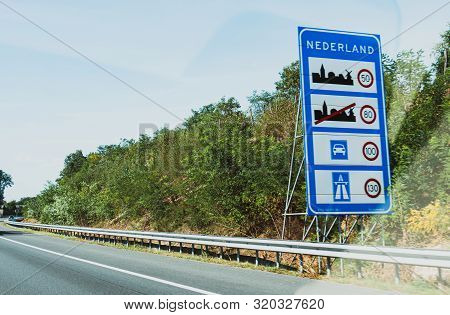 Nederland Text At The Border Between Germany And Netherlands With Speed Limits In City, Highway And