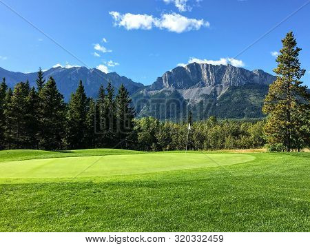 A View Of A Well Manicured Golf Green With Trees And The Rocky Mountains In The Background.  It Is A