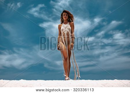 Beautiful Young Woman In White Exotic Dress On The Beach