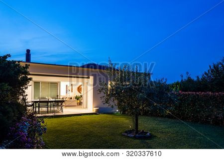 Exterior of a small modern house with garden. Night situation