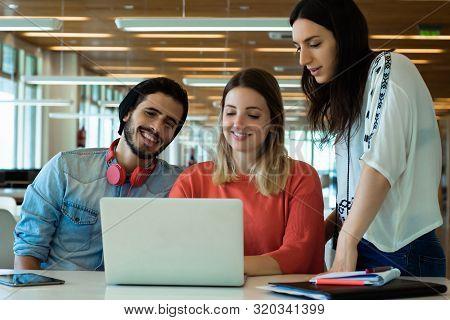 University Students Using Laptop In University Library.