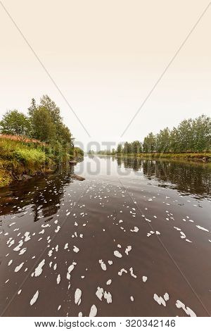The River Flows Slowly On A Misty Autumn Morning In The Rural Finland. There Is Some Kind Of Foam On
