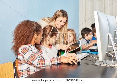 Group student and teacher in computer lessons of elementary school