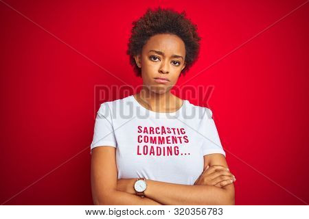 African american woman wearing sarcastic comments t-shirt over red isolated background skeptic and nervous, disapproving expression on face with crossed arms. Negative person. poster