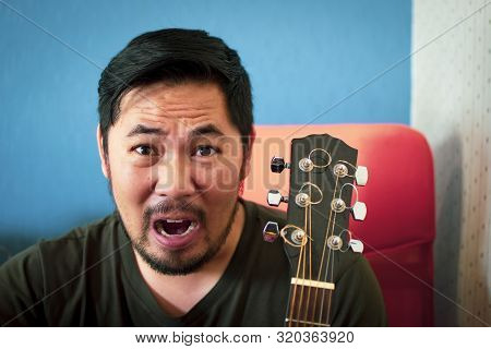 Bearded Man Shout And Headstock Of Acoustic Guitar With A Blue And White Color Blurred Backdrop In S