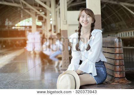 Beautiful Young Teenage Tourist Sit On A Bench At The Train Station Platform.