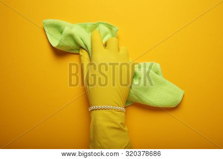 Discrimination and humiliation of women, hand with pearl bracelet in glove cleans. Woman housework, gender equality. poster