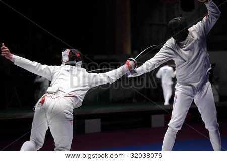 KIEV, UKRAINE - APRIL 14, 2012: Fight between Fabian Kauter, Switzerland and Weston Kelsey, USA during World Fencing Championship on April 14, 2012 in Kiev, Ukraine