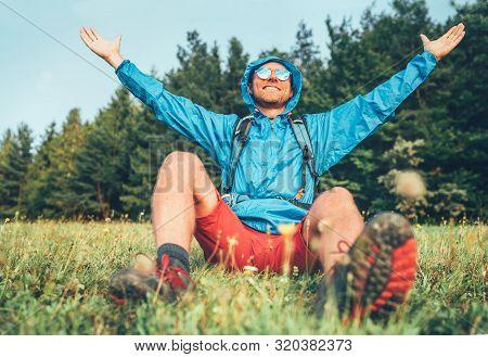 Backpacker Man Has A Rest Break Enjoying Mountain Landscape Wide Opened And Raised Arms. He Wears In