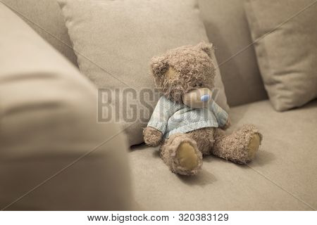 Lonely Teddy Bear Is On The Brown Sofa. Lonely Doll