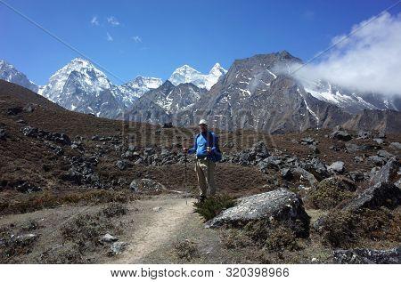 Trekker is standing on the trail to Ama Dablam base camp - acclimatization day trip from Pangboche village, Everest trek, Sagarmatha national park, Solukhumbu, Nepal