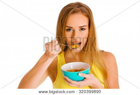 Blond woman eating cereals from bowl with spoon. Healthy breakfast for weightloss.