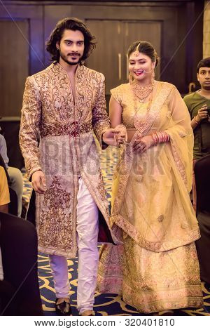 Indian Groom Dressed In Sherwani With Stunning Bride Standing With Glamorous Outfit And Jewellery Wi