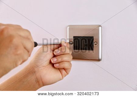Close-up Shot Of A Female Electrician Unscrewing A Light Switch