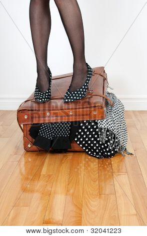 Woman In High Heel Shoes Standing On Overfilled Suitcase