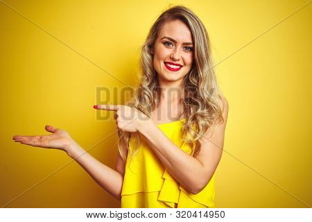 Young attactive woman wearing t-shirt standing over yellow isolated background amazed and smiling to the camera while presenting with hand and pointing with finger.