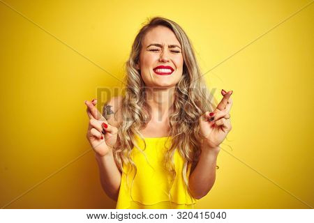 Young attactive woman wearing t-shirt standing over yellow isolated background gesturing finger crossed smiling with hope and eyes closed. Luck and superstitious concept.