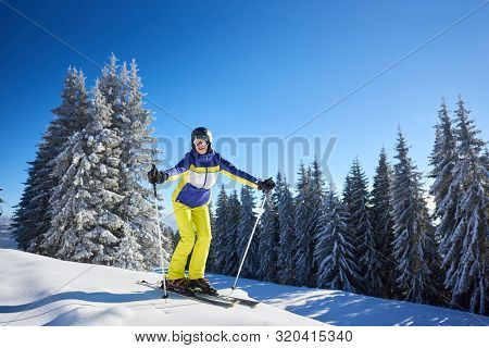 Young Happy Smiling Woman Posing On Skis In Goggles Looking On Camera Before Skiing From High Snowy