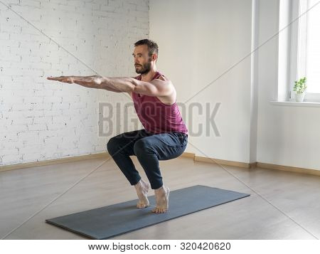 Chair Pose. Caucasian Fit Man Stands On Tiptoe And Doing Yoga In Fitness Studio, Selective Focus.