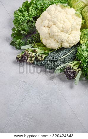 Different Kinds Of Fresh Organic Cabbage On A Gray Concrete Background. Green And Purple Kale, Brocc