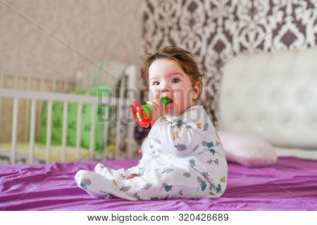 Baby Nibbles A Toy. Closeup Portrait Little Cute Girl With Big Blue Eyes With A Toy In Her Hands, Ni