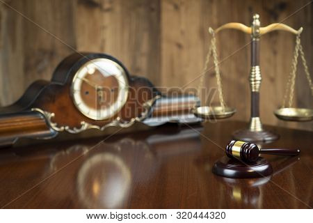 Law Concept. Gavel Of  The Judge, The Clock And The Scale On The Wooden Background.