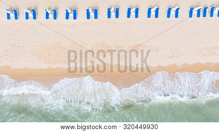 Aerial Top View On The Sandy Beach. Umbrellas, Sand, Beach Chairs And Sea Waves.