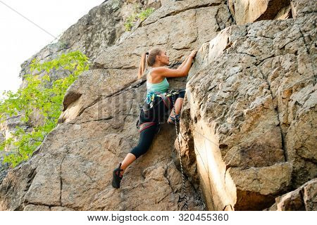Beautiful Woman Climbing on the High Rock in the Mountains. Adventure and Extreme Sport Concept