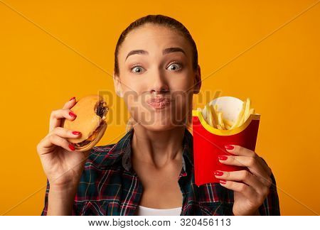 Hungry Girl Eating Burger And French-fries On Yellow Background. Cheat Meal And Junk Food. Studio Sh