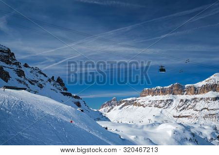 poster of View of a ski resort piste with people skiing in Dolomites in Italy with cable car ski lift. Ski area Arabba. Arabba, Italy