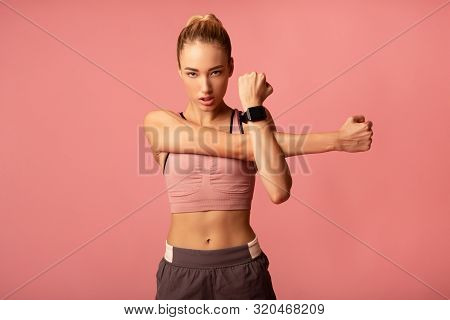 Determined Young Lady Doing Deltoid Arm Stretch Exercise Standing On Pink Studio Background. Copy Sp