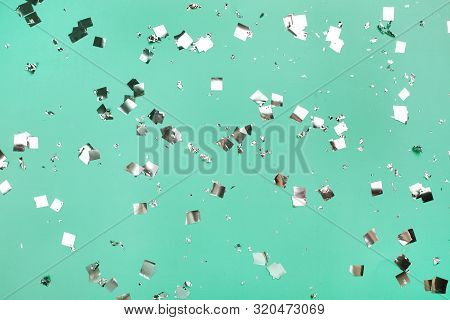 Falling Silver Confetti On Mint Backdrop. Holiday Concept.