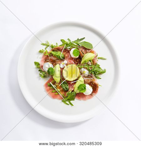 Tuna carpaccio with avocado and lime top view. Fish and citrus fruit slices on plate. Salmon and herbs leaves isolated on white background. Prepared restaurant gourmet meal. Served food composition