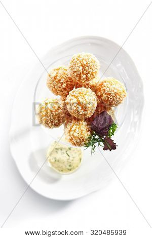 Top View of breaded cheese balls with mozzarella, cottage cheese and Tartar sauce in transparent bowl isolated on white background. Traditional Italian stuffed rice cheese balls arancini topview