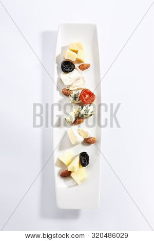 Cheese assorti platter top view. Gorgonzola, brie, parmesan and chevre slices. Cow and goat milk chopped cheese on plate. Served delicious snacks composition isolated on white background