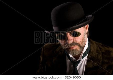Middle aged man in vintage sunglasses pince nez and bowler hat
