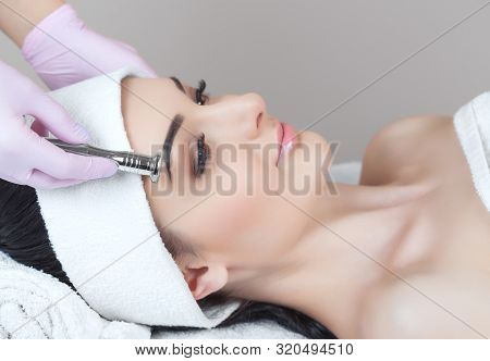 There is a woman, who is making the procedure Microdermabrasion of the facial skin in a beauty salon.Cosmetology and professional skin care. poster