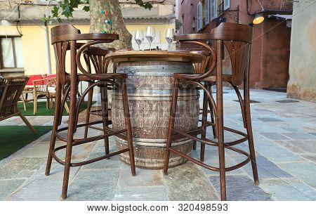 Highchairs With Barrel Table In Traditional Street Cafe On Coast Of Corsica Island , France.